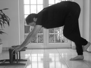 Fersenspor Behandlung mit dem vereinfachten herabschauenden Hund mit Hilfe eines Hockers